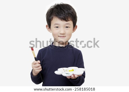 one asian boy child holds painting brush and colour palette with white background - stock photo