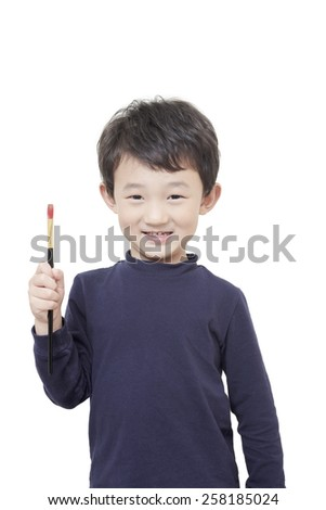 one asian boy child holds painting brush with white background - stock photo