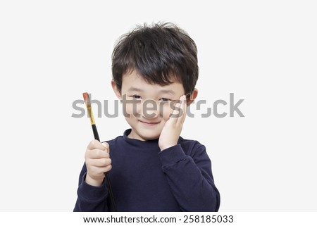 one asian boy child holds painting brush with white background