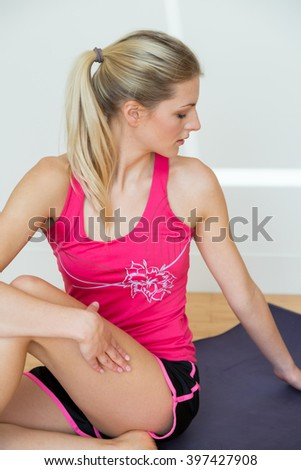 One athletic young woman wearing pink top and black shorts stretches her torso seated on a yoga mat near white wall - stock photo