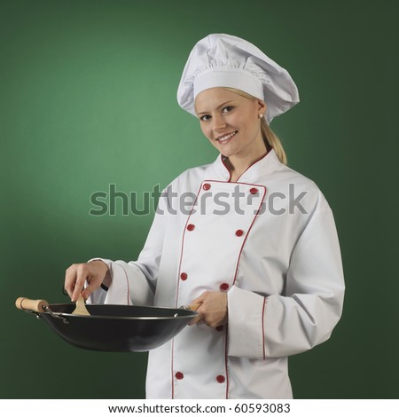 one atractive cook, she is wearing professional uniform and standinga wok - stock photo