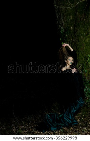 One attractive enigmatic glamour young woman with long hair and emeral bright makeup with bare shoulder in dress near tree trunk with green moss in evening forest outdoor copy space, vertical picture - stock photo