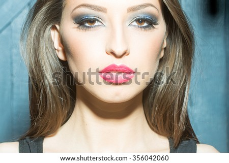 One attractive sensual fashionable young brunette pensive woman with bright makeup and beautiful hair in black underwear standing indoor in studio on wooden wall background, horizontal picture - stock photo
