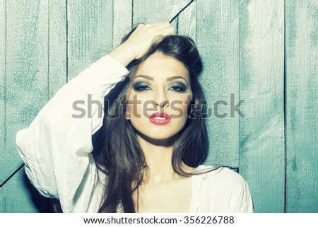 One attractive sensual fashionable young brunette pensive woman with bright makeup and beautiful hair in white blouse standing with raised hand in studio on wooden wall background, horizontal picture - stock photo