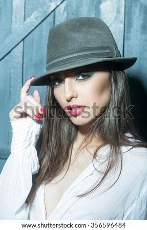 One attractive sensual fashionable young brunette pensive woman with bright makeup and beautiful hair in white blouse holding hat with hand in studio on wooden wall background, vertical picture - stock photo