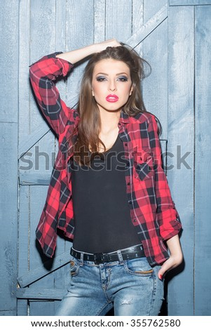 One attractive sensual fashionable young brunette pensive woman with straight body in black underwear and checkered red shirt standing indoor in studio on wooden wall background, vertical picture - stock photo