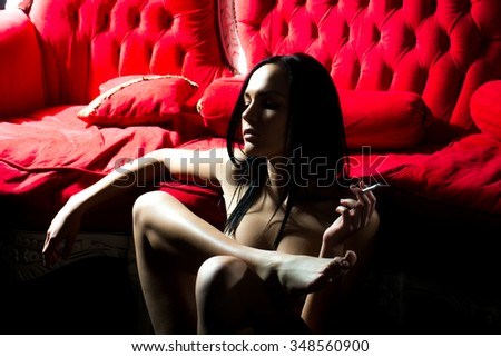 One attractive sexual undressed brunette young girl with slim body and long hair smoking cigarette sitting indoor in studio near red classic couch looking away, horizontal picture - stock photo