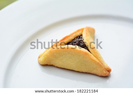 One backed Hamentashen, Ozen Haman, Purim cookie on a white plate for the Jewish holiday Purim.(Copy space) - stock photo