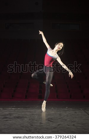 One ballerina practising on stage. Standing on one leg.