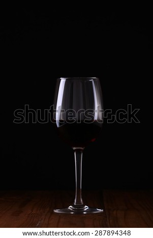 One beaker of red wine on wooden table top on black background, vertical picture - stock photo