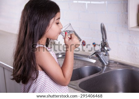 One beautiful middle eastern little girl with pink dress and long dark brown hair and eyes on white kitchen, helping parents to wash dishes and drinking water and smiling.  studio shot. - stock photo