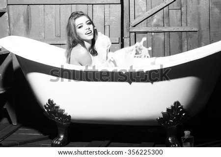 One beautiful sensual playful flirtatious young woman with long hair in knitted cloth sitting in white bath tub playing with soap foam indoor on wooden background black and white, horizontal picture - stock photo