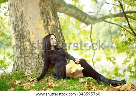 One beautiful sensual sexy slim brunette pensive woman sitting in autumn forest outdoor in long black dress on natural background, horizontal picture