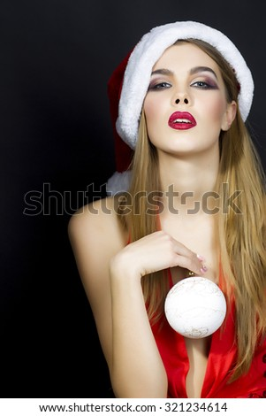 One beautiful sexual young blonde woman in red dress hat of santa with white fur and decorative new year tree ball holding in hands standing in studio on black background, vertical picture - stock photo