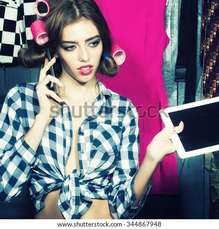 One beautiful sexy young stylish woman in checkered shirt with hair-rollers on head with laptop and mobile phone standing in wardrobe among many bright clothes, square picture - stock photo