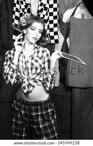 One beautiful sexy young stylish woman in checkered shirt with hair-rollers on head with laptop and mobile phone standing in wardrobe among many bright clothes black and white, vertical picture - stock photo