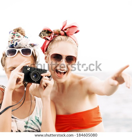 one beautiful smiling girl shows her pretty girlfriend with camera object to shoot - stock photo