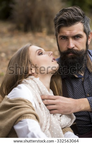 One beautiful stylish tender couple of young woman and senior man with long black beard embracing close to each other outdoor in autumn on natural background, vertical picture