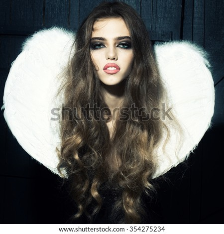 One beautiful tender dreaming young fashionable woman with long curly hair bright makeup and white fluffy angel wings with white feathers on back in black cloth dress on wooden background, vertical - stock photo