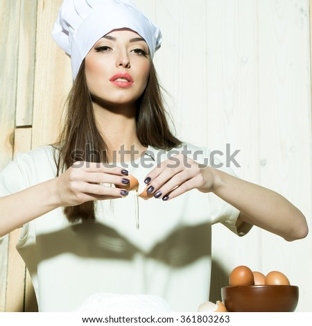 One beautiful young female cook in professional white uniform of hat and apron cooking homemade food making dough of flour and eggs in kitchen on wooden background, square picture
