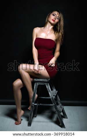 One beautiful young sexual woman with long wet curly hair and straight slim body in erotic dress. Girl with perfect slim body. Wet hair. Sexy girl sitting on a chair in the studio  - stock photo