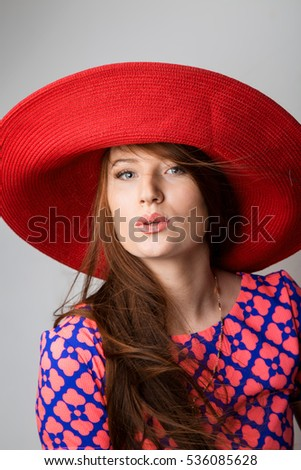 One beautiful young woman blowing a kiss in red blue dress and red retro hat isolated white grey background . Studio shot, vertical image picture