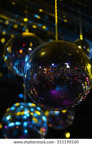 One big and many other beautiful mirrored round disco ball on ceiling in colorful lights yellow blue colors in club indoor on black shining background, vertical picture - stock photo
