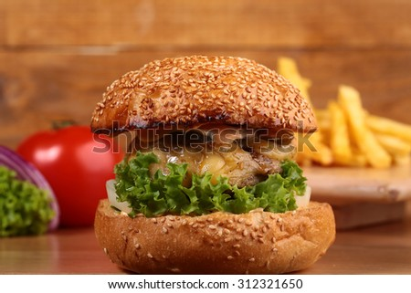 One big delicious fresh burger of green lettuce red tomato cheese meat cutlet violet oinion and white bread bun with sesame seeds on wooden background closeup, horizontal picture - stock photo
