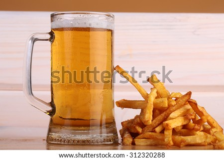 One big glass bocal of light cold delicious beer with white froth and tasty crispy yellow potato fasfood chips on wooden background closeup, horizontal picture - stock photo