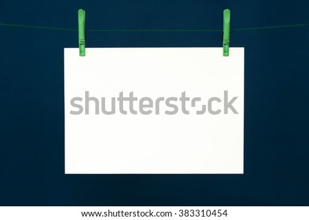 One big paper card hanging on the green rope on blue background.