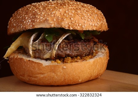 One big tasty appetizing fresh burger of green lettuce red tomato cheese and bacon slice meat cutlet and white bread bun with sesame seeds closeup, horizontal picture - stock photo