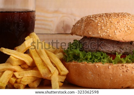 One big tasty appetizing fresh burger of green lettuce red tomato cheese and bacon slice meat cutlet and white bread bun with sesame seeds with cola and potato chips, horizontal picture - stock photo