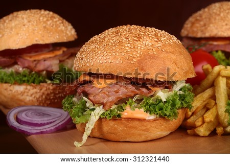 One big tasty appetizing fresh burger of green lettuce red tomato cheese bacon slice meat cutlet violet oinion and white bread bun with sesame seeds on wooden table closeup, horizontal picture - stock photo