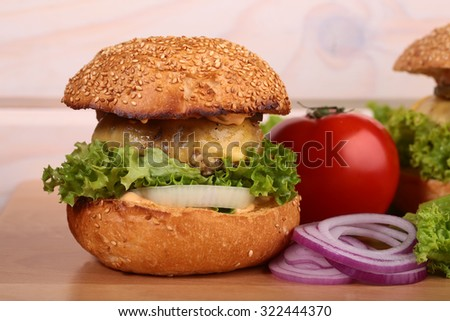 One big tasty appetizing fresh burger of green lettuce red tomato cheese bacon slice meat cutlet violet onion and white bread bun with sesame seeds on wooden table closeup, horizontal picture - stock photo