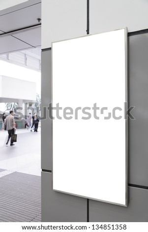 One big vertical / portrait orientation blank billboard on gray wall with blued passenger background - stock photo