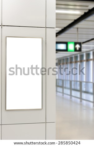 One big vertical / portrait orientation blank billboard on modern white wall with corridor background - stock photo