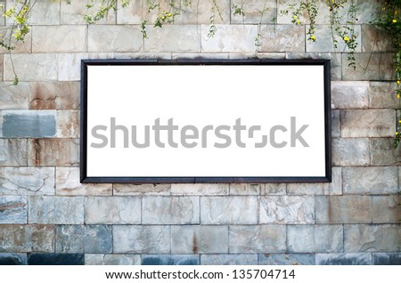 One blank billboard attached to a buildings exterior brick wall. - stock photo
