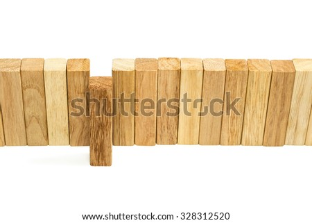 One block of wood pushed forward among other such bars lined in a row standing isolated on white background - stock photo