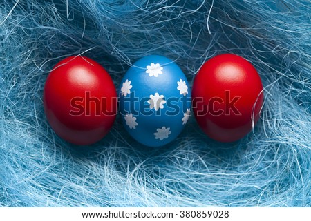 One blue Easter egg and red eggs on blue background - stock photo