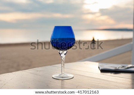 One blue glass closeup on table concept of solitude with romantic sunset on the beach in background