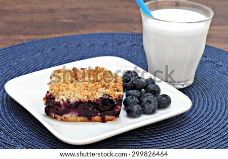 One blueberry cookie bar with a streusel topping and a glass of milk. - stock photo