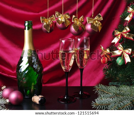 One bottle  and  two  goblets of champagne with new year decorations against purple drapery. Happy New Year! - stock photo