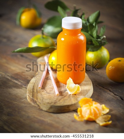 One bottle of fresh tangerine juice with ripe tangerines, leaves and old-fashioned straws - stock photo