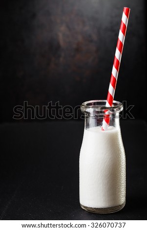One bottle with milk on dark background with  striped straw