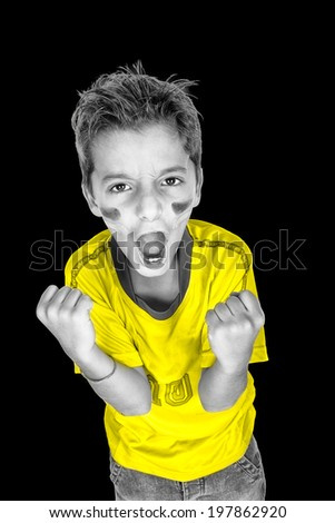one brazilian soccer football fan kid screaming goal in black and white with yellow shirt. Studio, isolated on black background