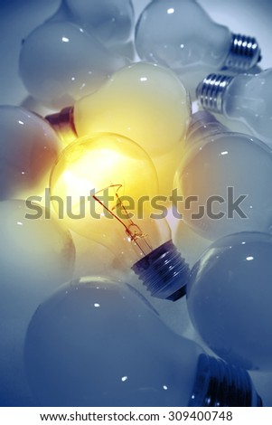 One bright bulb in line of dull light bulbs. Standing out concept  - stock photo