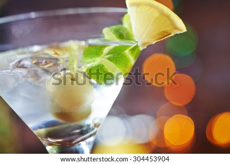 one bright delicious glass of cold martinis with olives on a wooden table in a restaurant or bar with creative decoration lime and lemon. soft focus and beautiful bokeh. - stock photo