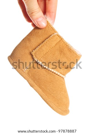 One brown winter boot in women hand on pure white background
