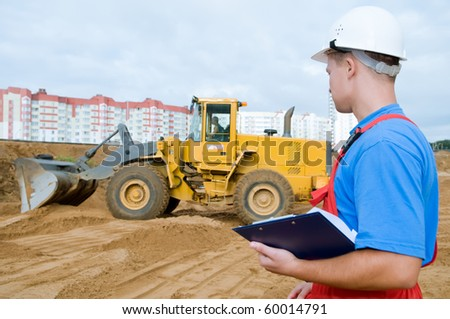 One builder worker with clipboard inspecting earthmoving works at construction site. Focus on worker