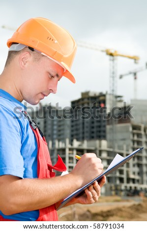 One builder worker writing in clipboard inspecting works at construction site - stock photo